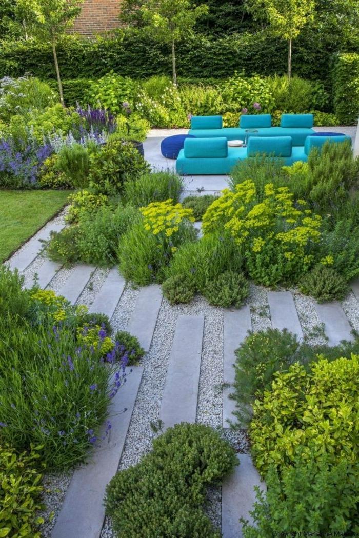 zwei blaue Sofas, ein grüner Garten mit bunten Blumen, Platten in grauer Farbe, moderne Gartengestaltung