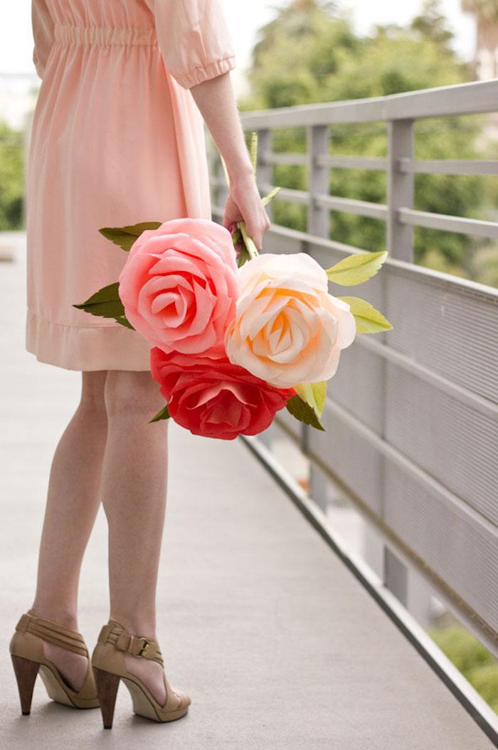 Drei riesige Papierrosen, rot weiß und rosa, Frau mit Kleid in Rosa und Schuhen in Beige