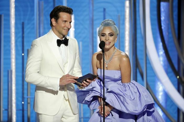 Bradley Cooper und Lady Gaga, schön gekleidet, Lady Gaga mit einem blauen Kleid und Bradley mit weißem Anzug