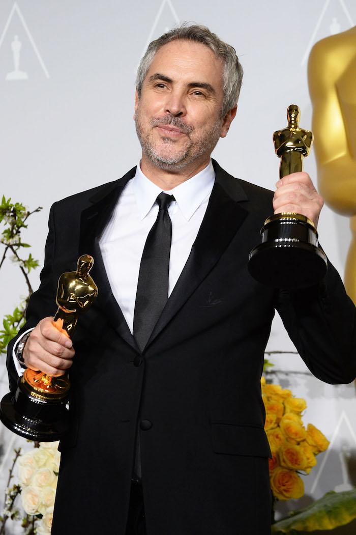 mann mit einem schwarzen anzug und einem weißen hemd und schwarzer krawatte und mit zwei goldenen oscars, der regisseur von roma alfonso cuaron