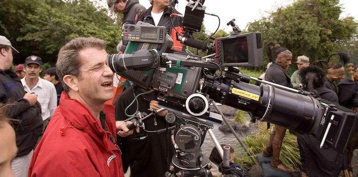 wald mit grünen bäumen, der schauspieler mel gisbon mit einer roten jacke und einer großen schwarzen kamera