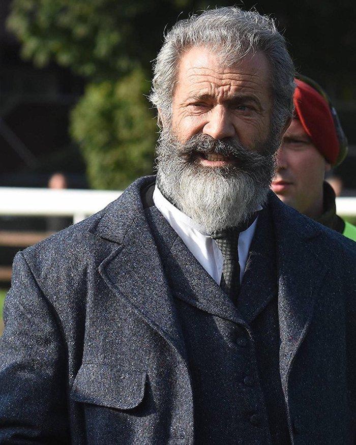 eine szene von dem film the professor and the madman, der schauspieler mel gibson mit einem grauen mantel und mit langem grauen bart