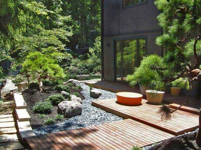 Terrassendiele, Kies Steine und kleine Bäume und Büsche, der Hinterhof eines Hauses, moderne Gartengestaltung