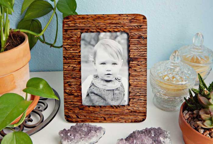 DIY Bilderrahmen aus Holz, süßes Baby auf dem Bild, grüne Zimmerpflanzen in Blumenkörben