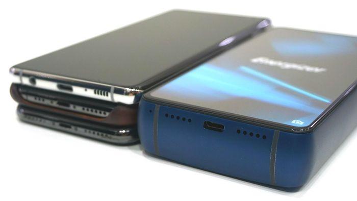 ein großes und dickes smartphone Energizer-P18K-Pop mit einem blauen bildschirm und drei dünne schwarze handys