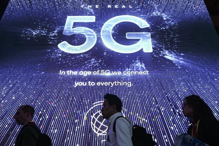 junger mann mit einem weißen hemd ein großer violetter bildschirm mit einem 5G-Logo, der mobile world congress 2019 in barcelona