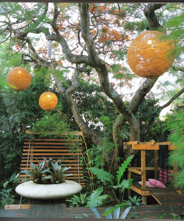ein Baum, auf dem orage Laternen hängen, grüne und rote Blätter, eine Vase, Bänke, moderne Gartengestaltung