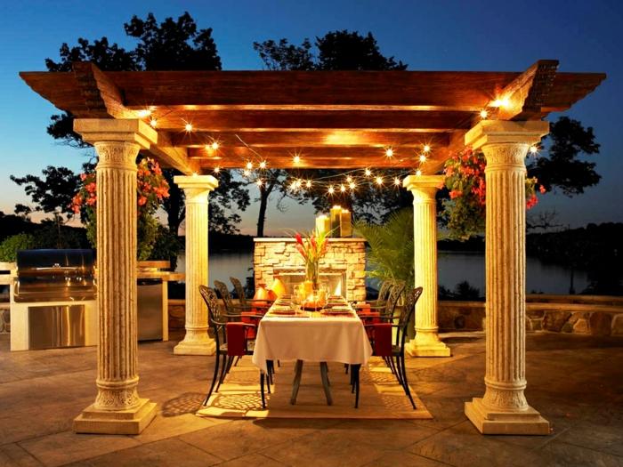 ein Garten voller schöne Lichter, ein für Party gedeckter Tisch, Säulen und ein Kamin, Gartengestaltung Ideen