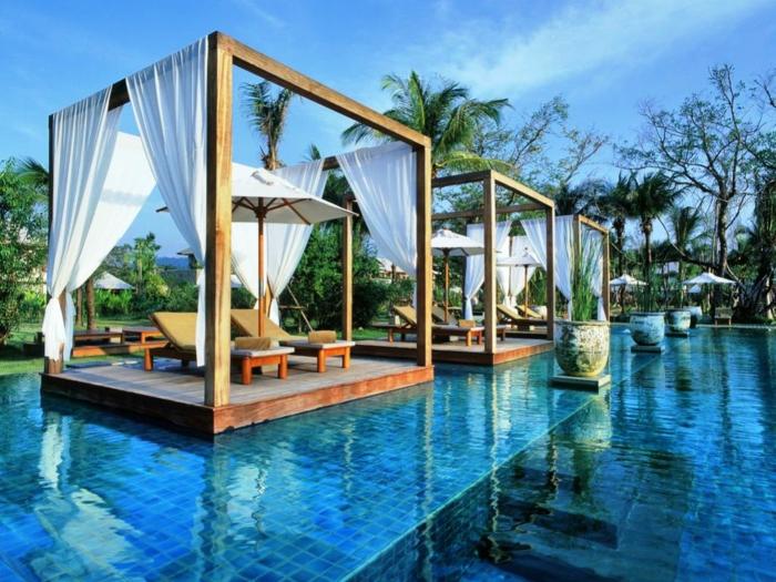 ein traumhafter Garten, Schwimmbad mit blauem Wasser, Häuschen mit Liegestühle und Ampelschirme,