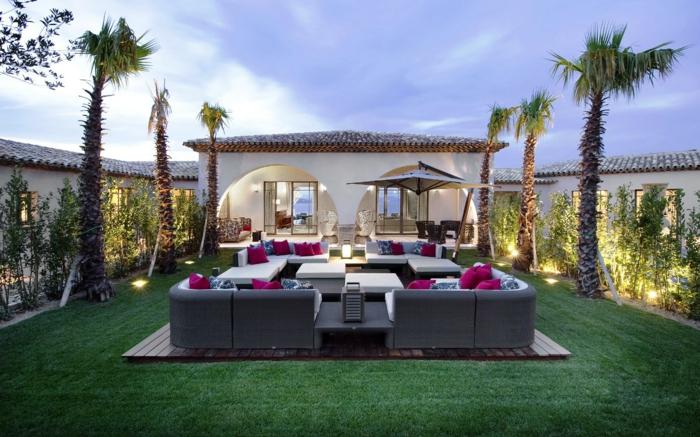 ein gepflegter Rasen, Loungemöbel mit rosa Kissen und blauen Kissen, Palmen, Garten gestalten