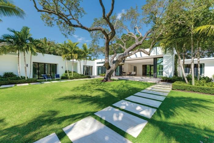 Garten gestalten, ein exotischer Garten, ein Baum und viele Palmen, ein Landhaus in weißer Farbe