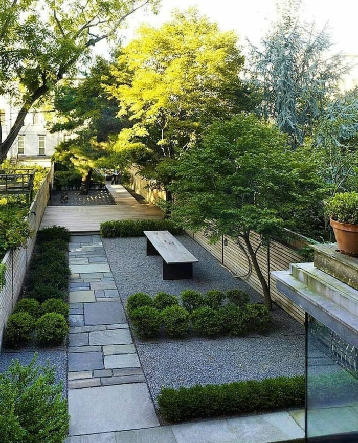 Kies und Stein, ein Sichtschutz aus Holz, drei Bäume, eine Bank, Garten gestalten im Herbst