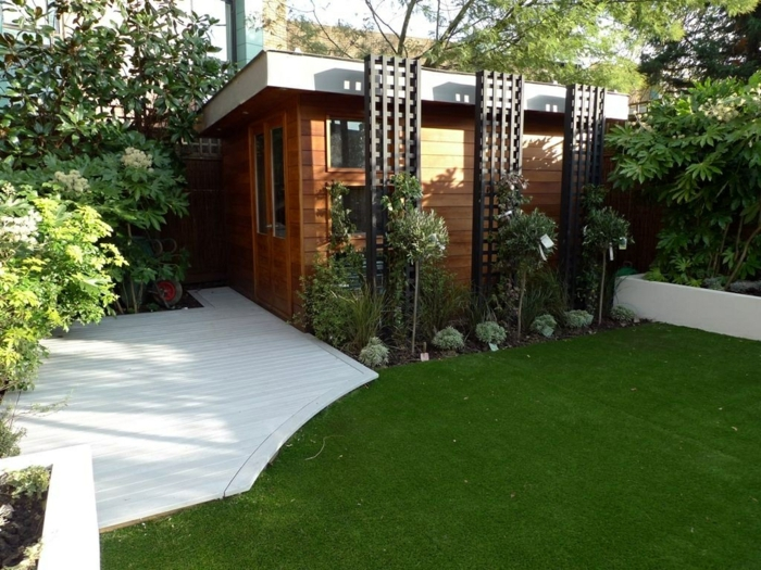 ein gepflegter Rasen, ein Häuschen, weiße Terrassendiele, kleine Bäume, Garten gestalten