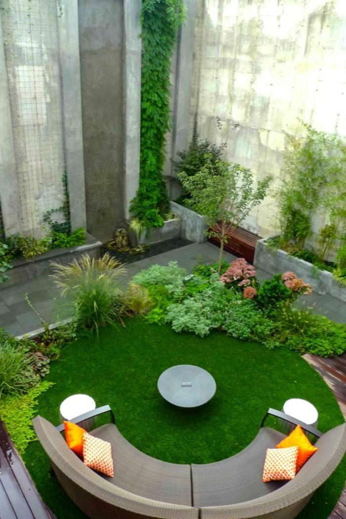 ein gepflegter Rasen in gerundeter Form, gerundete Loungemöbel, ein kleines Tischlein, viele Ziersträuche