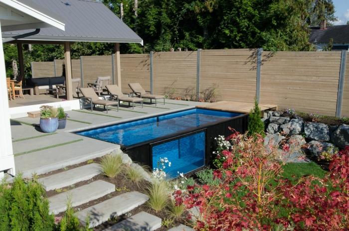 ein Schwimmbad mit klarem blauem Wasser, rote Blumen, drei Liegestühle, Garten gestalten, Treppen