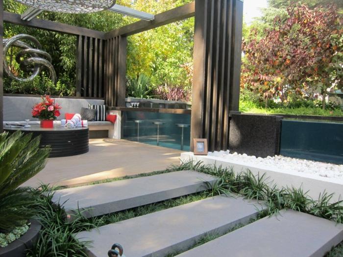 Kies Steine, große Platten, eine Theke, drei Hocker, ein runder Tisch, ein exotisher Pergola Garten gestalten