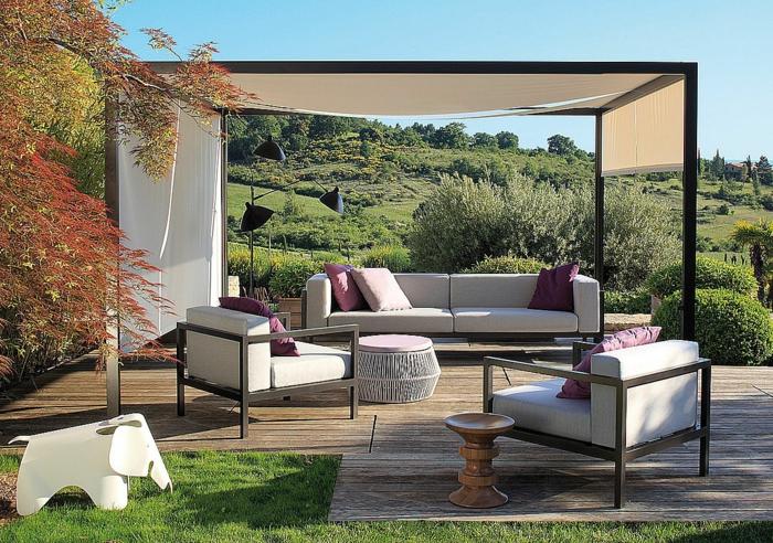 ein Pergola, weiße Loungemöbel mit lila und weiße Kissen, Terrassendiele, ein grüner Rasen, Garten gestalten