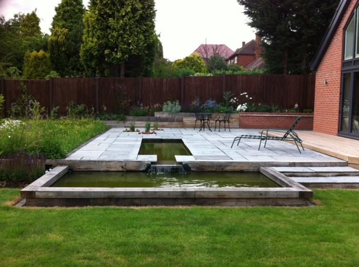 ein Teich mit Wasserspiel, weiße Fliesen, Tische und Stühle, ein Liegestuhl, ein Sichtschutz