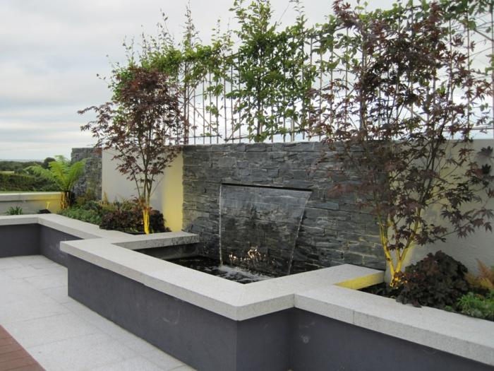 ein Wasserspiel auf einer grauen Wand, viele Bäume, Lichter, Fliesen in weißer und brauner Farbe, Garten gestalten