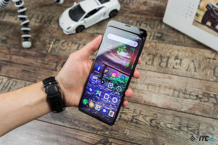 kleiner weißer wagen und eine hand mit einer schwarzen armbanduhr und einem schwarzen xiaomi smartphone Mi Mix 3