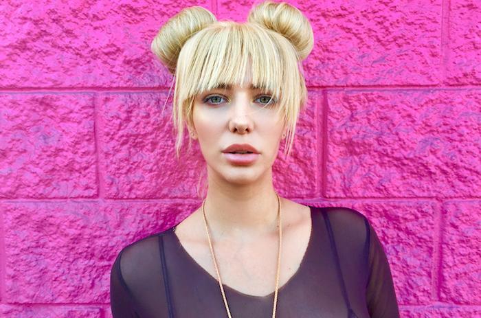 unser lied für israel, eine juge frau mit blauen augen und pinken lippen und einer langen goldenen halskette, eine pinke wand und blondes haar