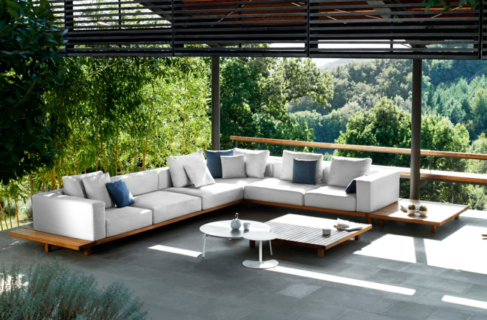 eine moderne Terrasse, Gartengestaltung Ideen, weiße Loungemöbel mit weißen und blauen Kissen, grüne Bäume