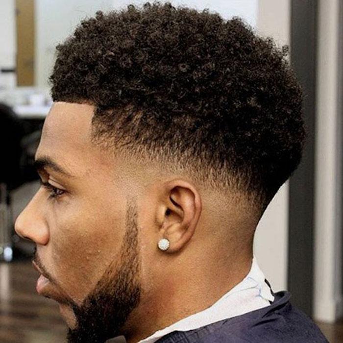 Frisuren mittellang stufig bei lockigen Haaren, kleine Locken, gerade Linien am Kopf, Mann mit Ohrring und kurzer fein gestalteter Bart