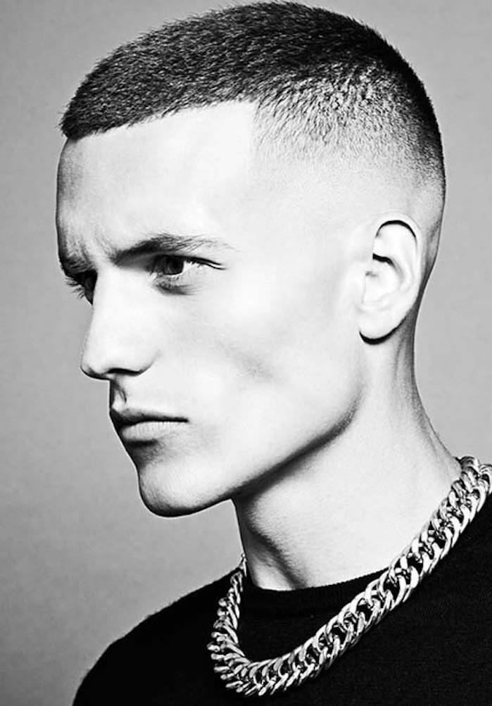 Frisuren halblang gestuft, schwarz weißes Bild von einem Mann mit Panzerkette und böses Gesicht, kurze Haare stufenartig gemacht