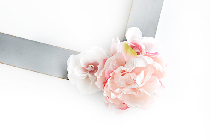 Holzrahmen mit grauer Acrylfarbe bestreichen, künstliche Blüten daran kleben, DIY Party Idee