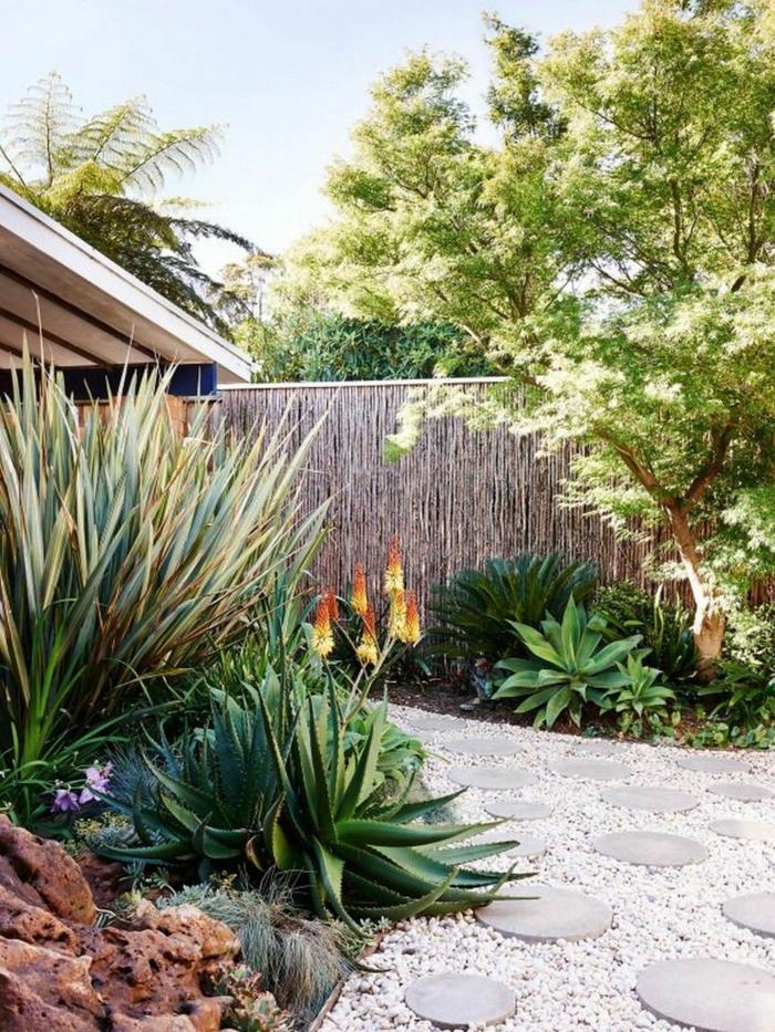Kiesweg mit runden grauen Steinen, hohe Ziersträucher, ein hoher Sichtschutz, Garten Ideen