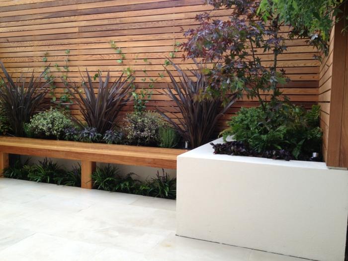 ein hoher Sichtschutz, ein Hochbeet in weißer Farbe, Garten Ideen für eine moderne Gestaltung