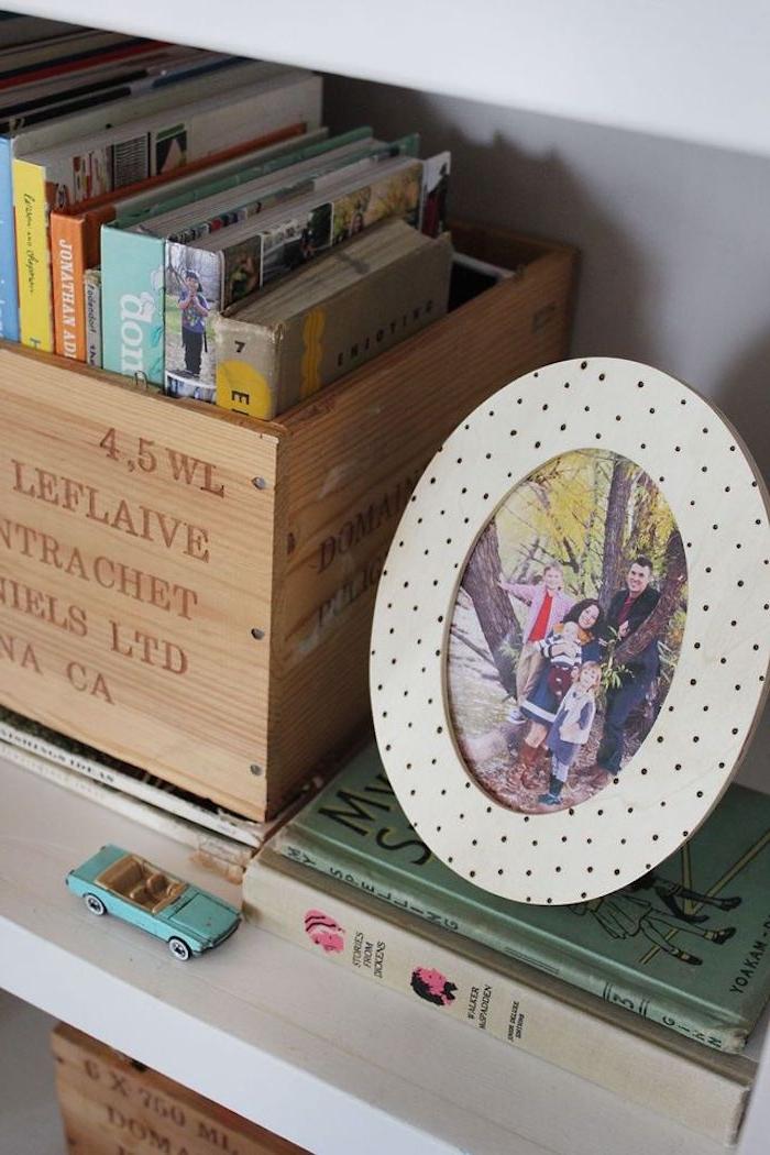 Runder Bilderrahmen aus Holz, schwarze Punkte daran, Bücher in Holzkiste, blaues Spielzeugauto