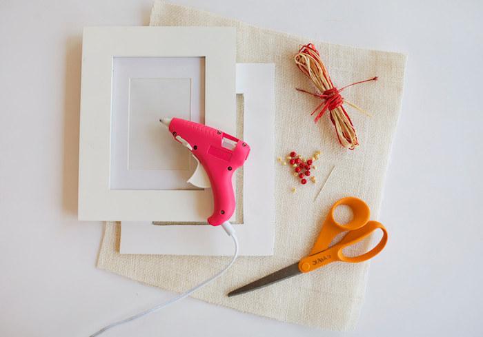 Bilderrahmen selber basteln, Materialien für DIY Projekt, weißer Holzrahmen, Heißklebepistole und Schere, Schnur und Perlen, weißes Stoff und Nadel