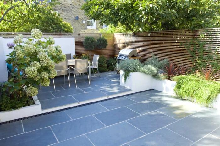 graue Fliesen, beige Gartenmöbel und ein hoher Sichtschutz, Gartengestaltung Bilder, weiße Blumen