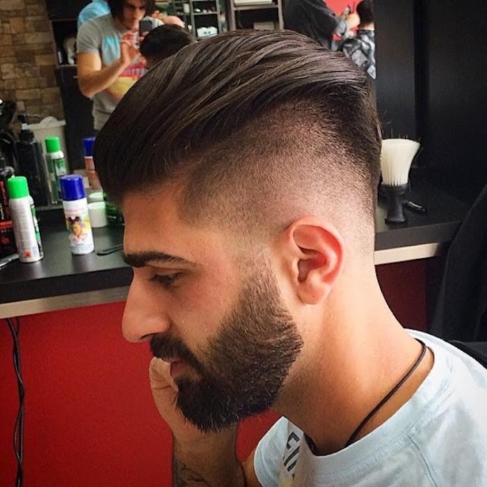 Stufenschnitt lange Haare, Haar nach hinten stylen, weißes Shirt, Bart, dunkle Augenbrauen, Mann im Frisörsalon