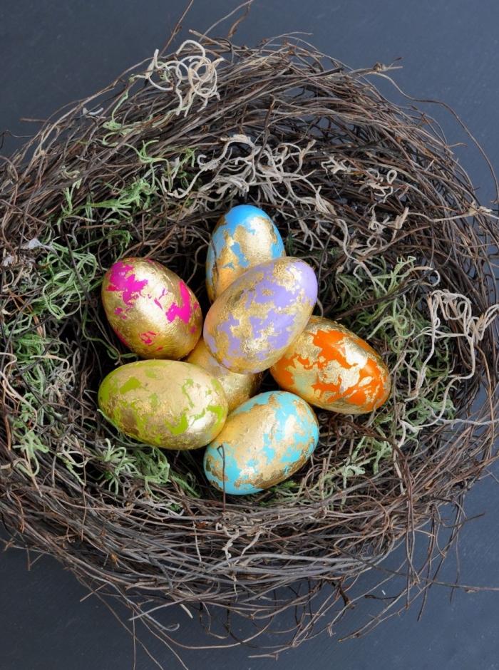selbstgemachtes nest aus moos und dünnen zweigen, körbchen basteln, eier dekoriert mit blattgold