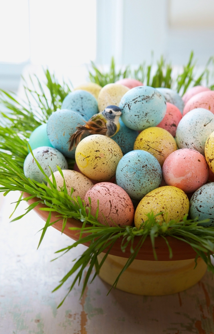 körbchen basteln zum ostern, große schüssel, küstliches gras, bunte eier, kleiner vogel