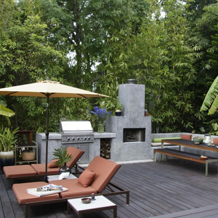 zwei Liegestühle, Terrassendiele, Ampelschirm, Kamin, viele grüne Bäume, Gartengestaltung Ideen