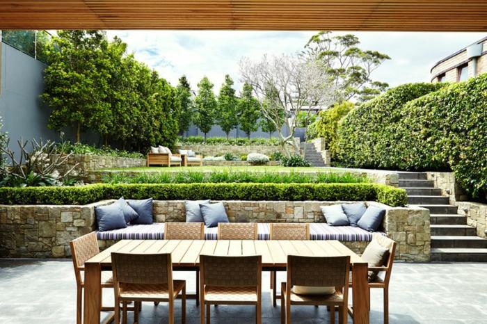 eine niedrige Hecke, Loungemöbel mit blauen Kissen, Esstisch, Bäume im Hintergrund, Gartengestaltung Ideen