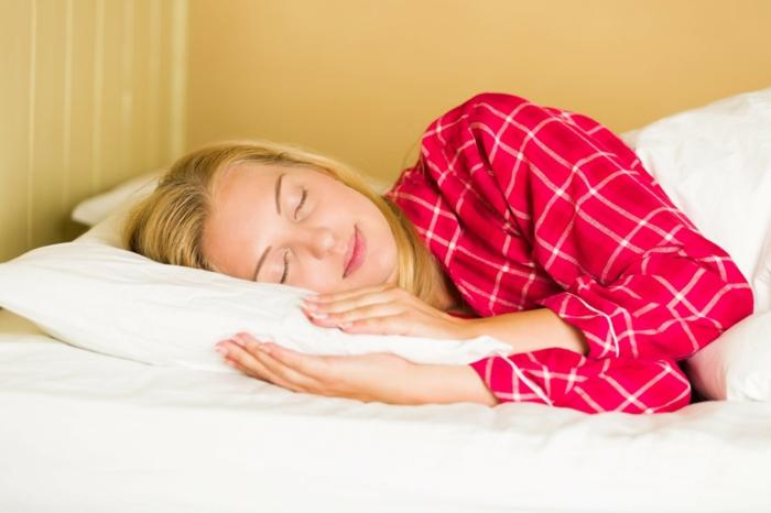 ein blondes Mädchen schläft auf einem weißen Kissen, sie trägt ein roter Schlafanzug