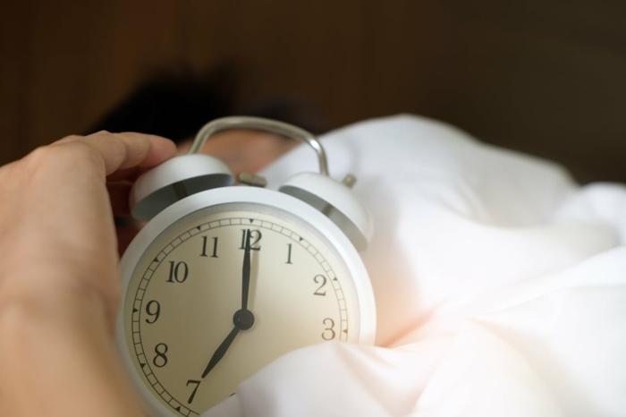 ein Wecker in weißer Farbe, eine weiße Bettdecke, eine Hand, bequeme Matratze
