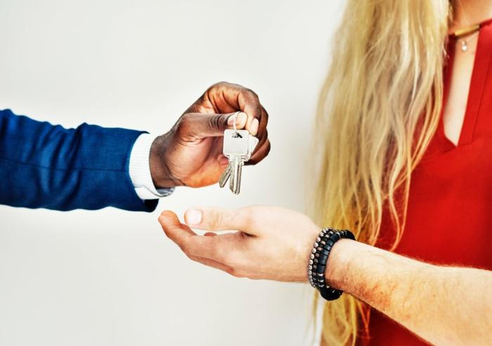 ein Schlüssel, Mädchen mit blondem Haar, eine Hand gibt den Schlüssel zu dem Mann, Mietrecht