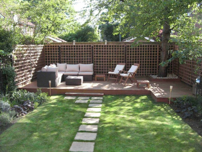 grüner Gras, schöne Loungemöbel mit weißen Kissen, hoher Sichtschutz, Gartengestaltung Beispiele
