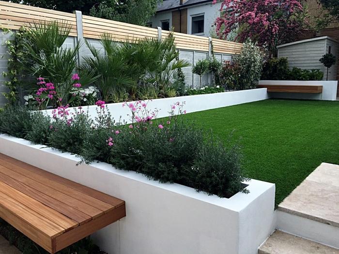 ein gepflegter Rasen, zwei Bänke, Hochbeete in weißer Farbe mit kleinen lila Blumen, Gartengestaltung Beispiele