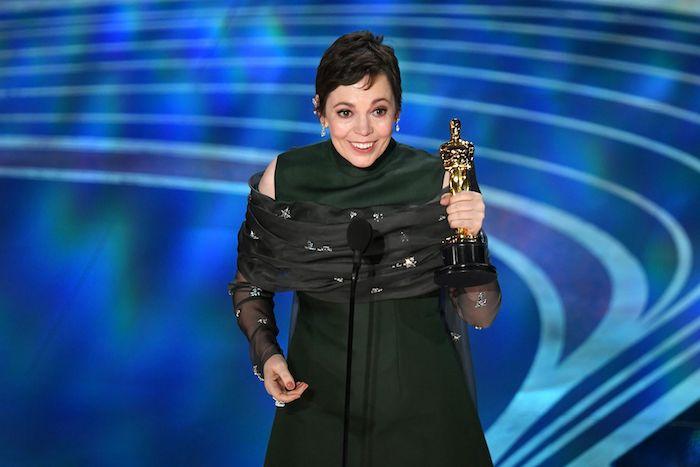 die schauspielerin olivia colman mit ihrem ersten goldenen oscar, frau mit einem grünen kleid, ohrringen und ringen