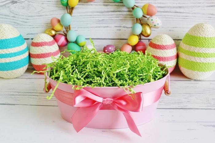 osterkörbchen basteln mit kindern, rosa korb gefüllt mit grünem papier, große schleife