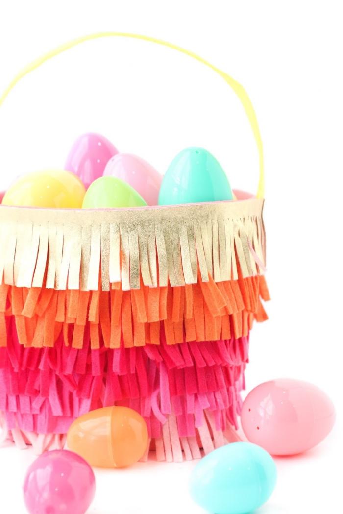 osterkörbchen selber machen, großer korb mit gelbem henkel gefüllt mit vielen bunten eiern