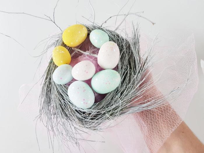 osternest basteln, nest aus zweigen, viele eier, rosa netz, diy deko zum ostern