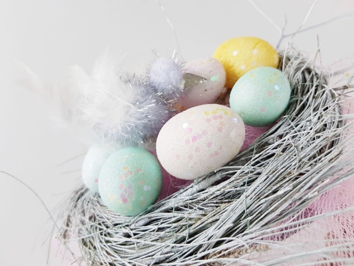osternest basteln, graue zweige, rosa netz, eier dekoriert mit glitzer, feder