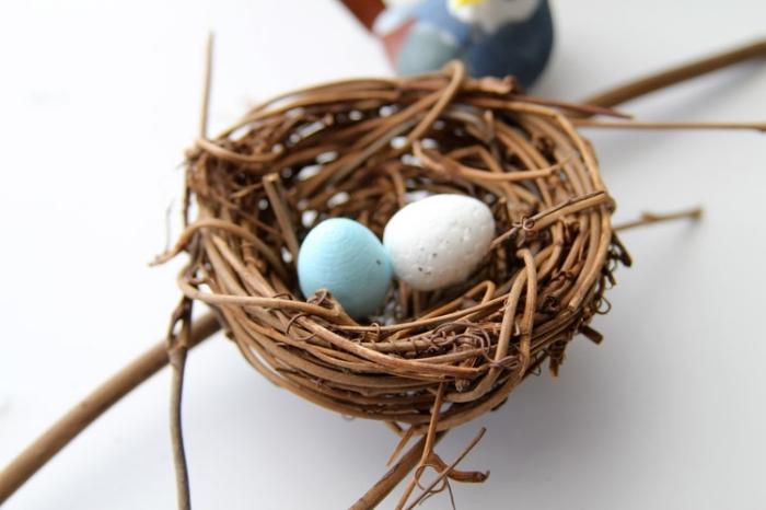 osternest basteln vorlage, zwei eier, selsbtgemachtes nest aus zweigen, bastelanleitung